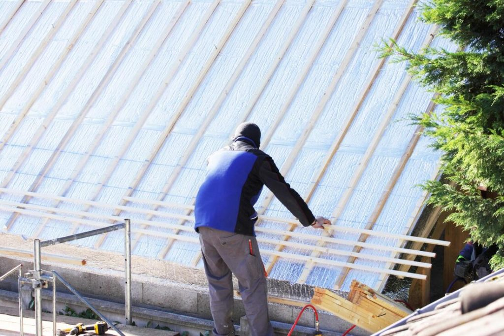 Guy Installing Slats to get ready to roof a commercial roof For Delaware County Roofers