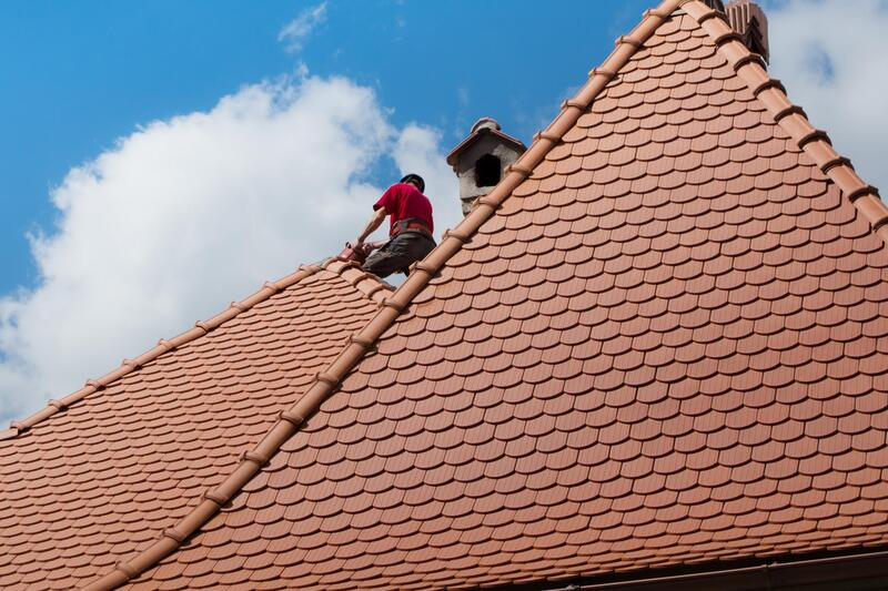 2 Men working on a high pitched roof just finishing up shingles For Delaware County Roofers