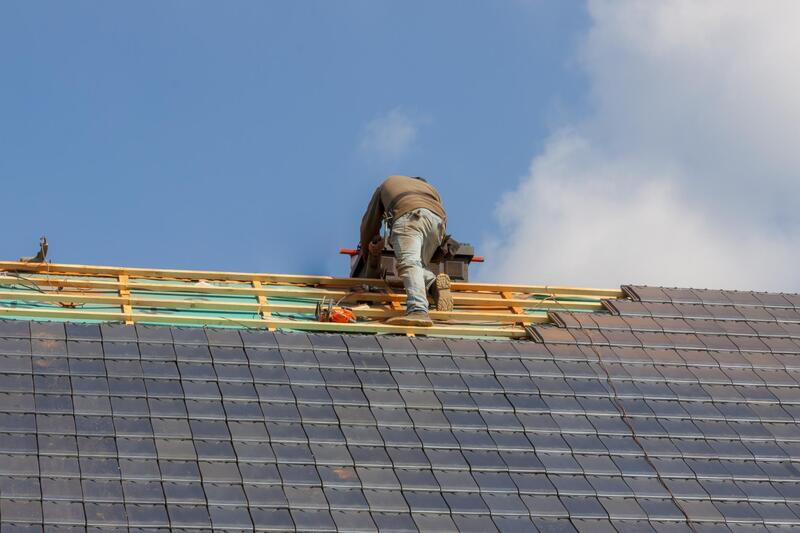 Man working on the last part of installing shingles onto a new roof working For Delaware County Roofers