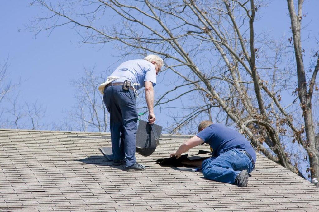 Two men working to repair a roof leak with some new shingles For Delaware County Roofers